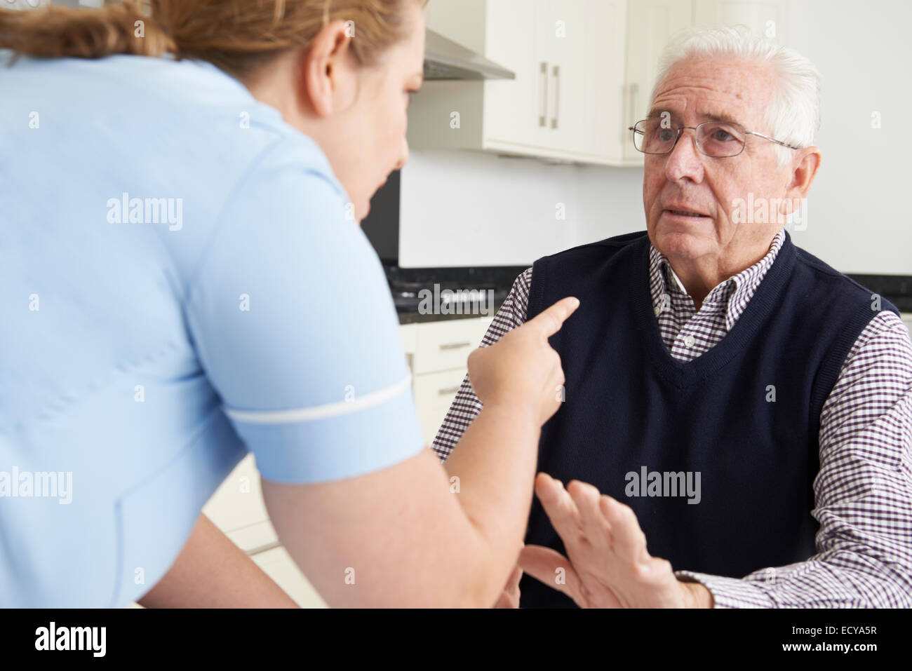 Care Worker Mistreating Elderly Man - Stock Image