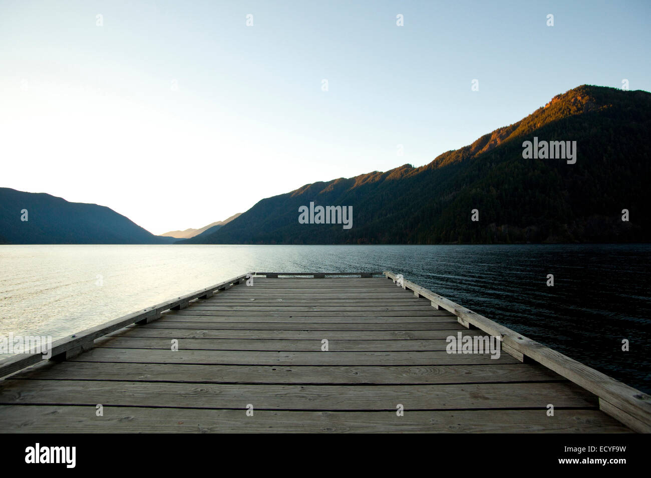 Wooden deck at lake under blue sky - Stock Image