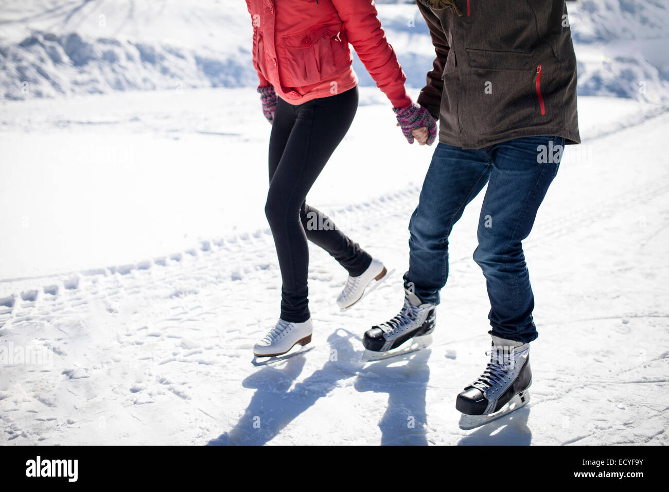 Caucasian couple ice skating on snowy frozen lake - Stock Image