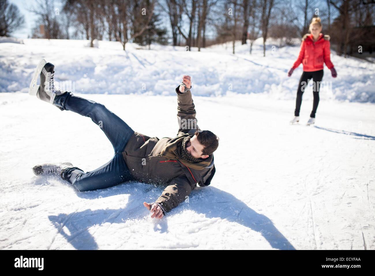 Caucasian man falling while ice skating on frozen lake - Stock Image