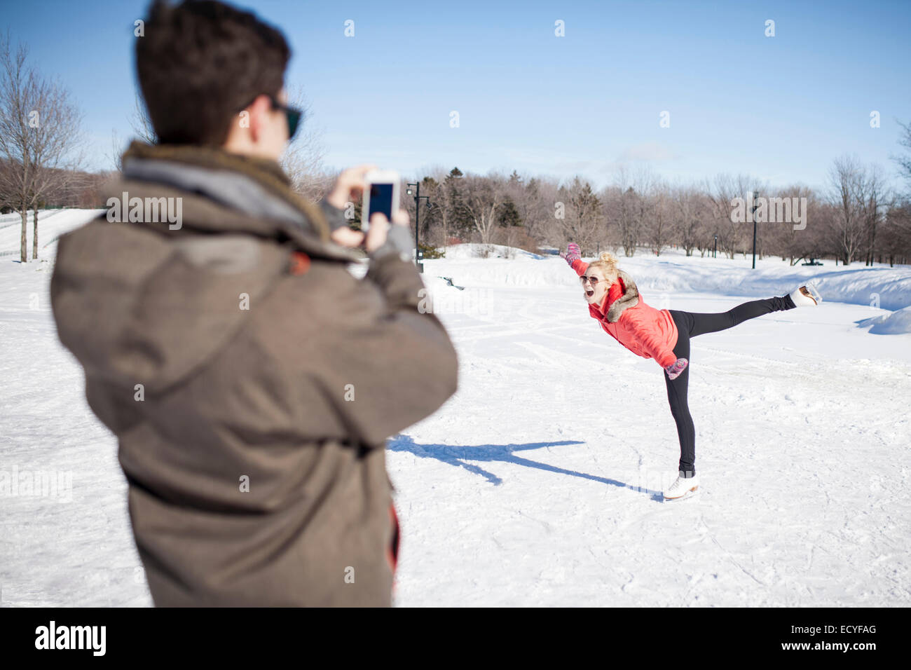 Caucasian man taking picture of girlfriend ice skating on frozen lake - Stock Image