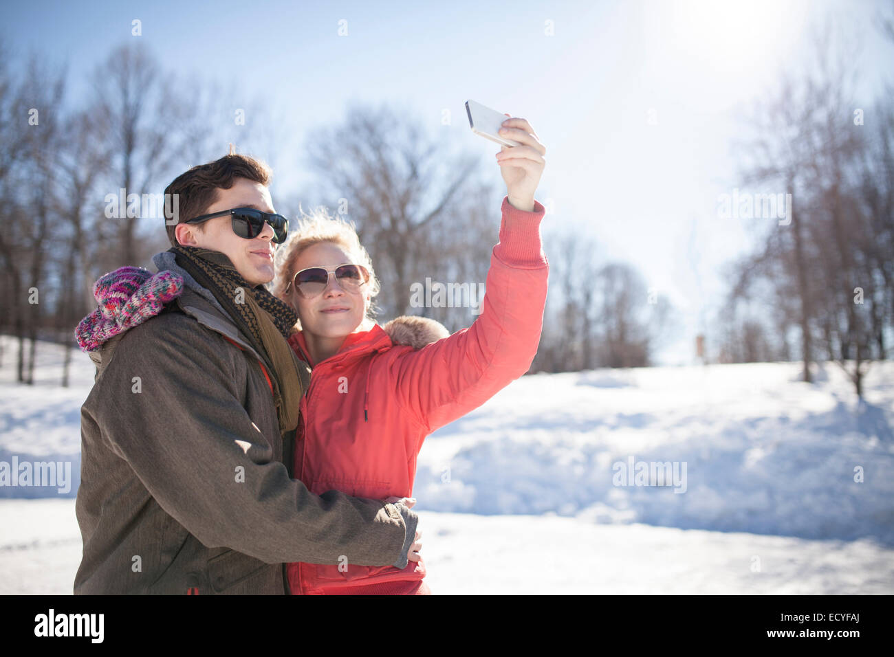 Caucasian couple taking cell phone selfie in winter Stock Photo