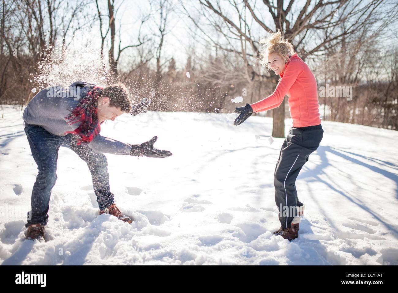 Caucasian couple having snowball fight - Stock Image