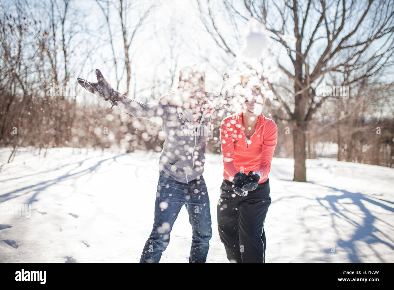 Caucasian couple throwing snowballs - Stock Image