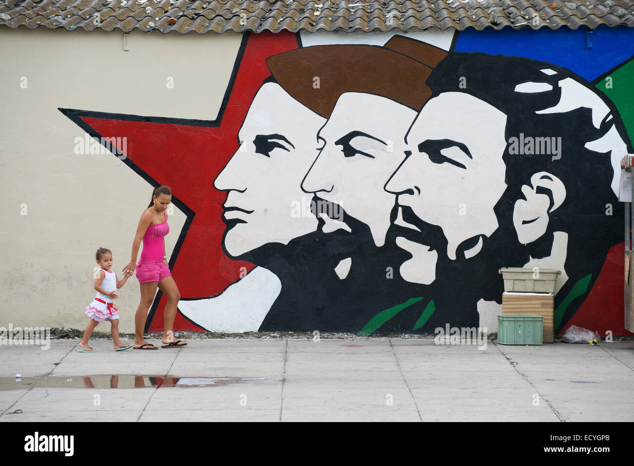HAVANA, CUBA - MAY 16, 2011: Cuban woman and child walk in front of billboard featuring Mella, Cienfuegos, and Guevara. - Stock Image