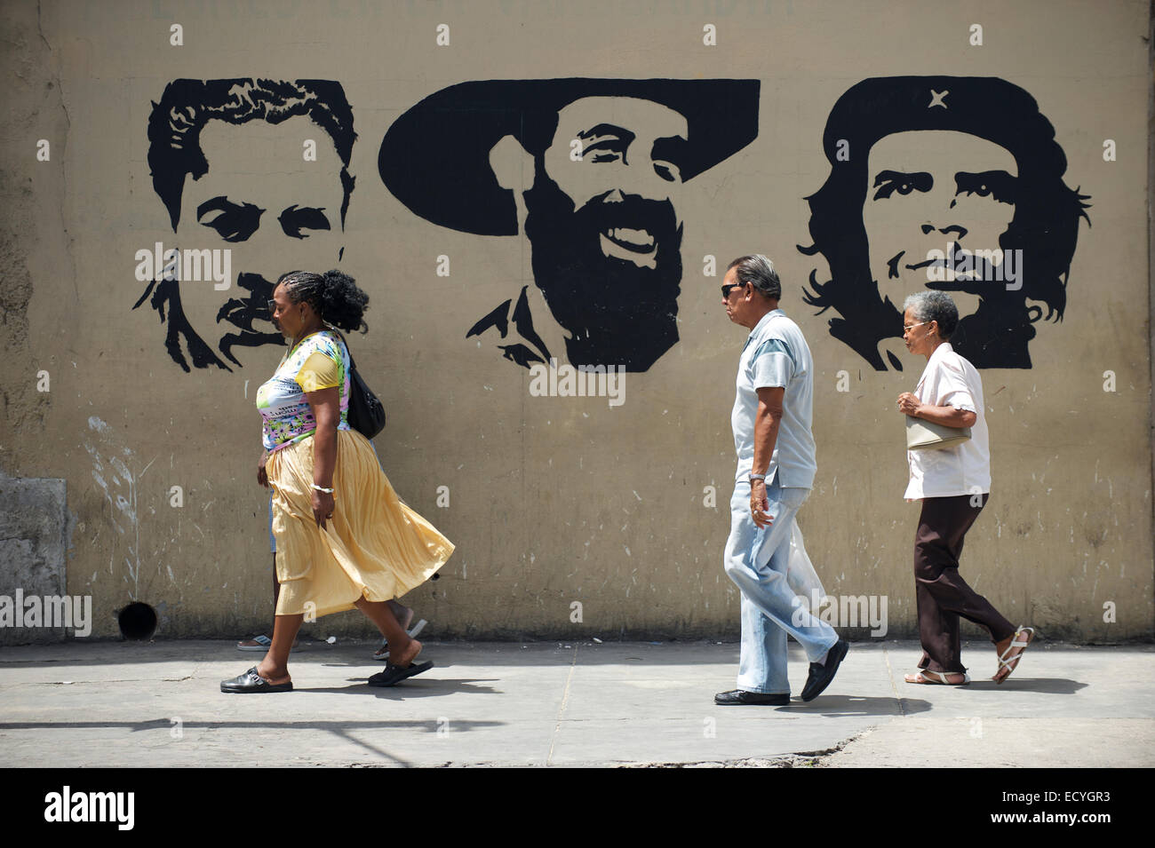 HAVANA, CUBA - MAY 16, 2011: Cuban people walk in front of billboard featuring revolutionaries Mella, Cienfuegos, - Stock Image