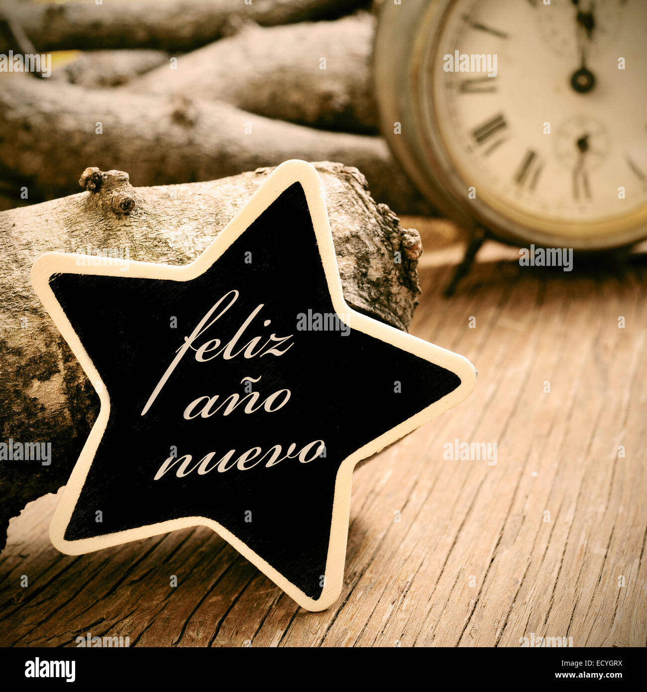 the sentence feliz ano nuevo, happy new year in spanish, written in a star-shaped chalkboard, on a rustic wooden - Stock Image