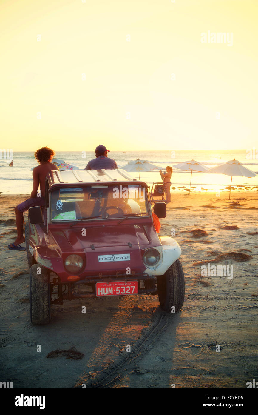 JERICOACOARA, BRAZIL - OCTOBER 8, 2013: Dune buggy stands on the beach at sunset on Jeri, a popular center for adventuring. - Stock Image