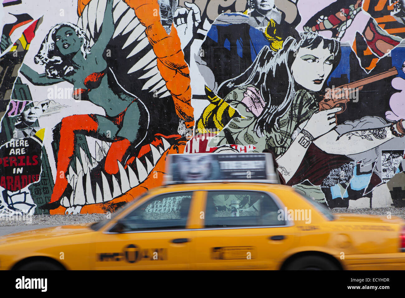A yellow New York City taxi cab drives east past the Bowery Mural