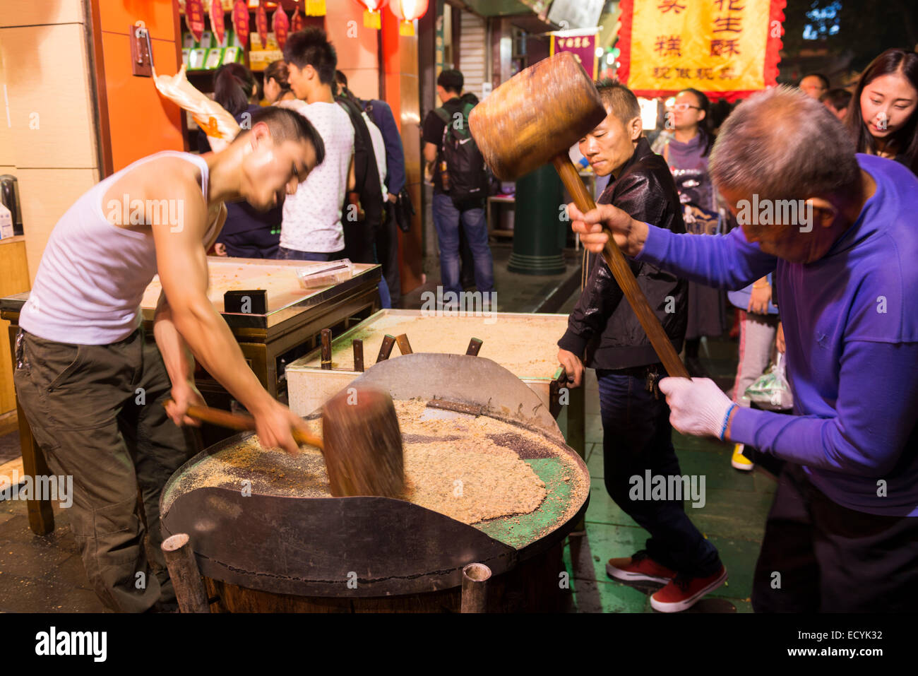 People making brittle candy at Bei Yuan Men Muslim food night market in Xi'an, Shaanxi, China 2014 - Stock Image