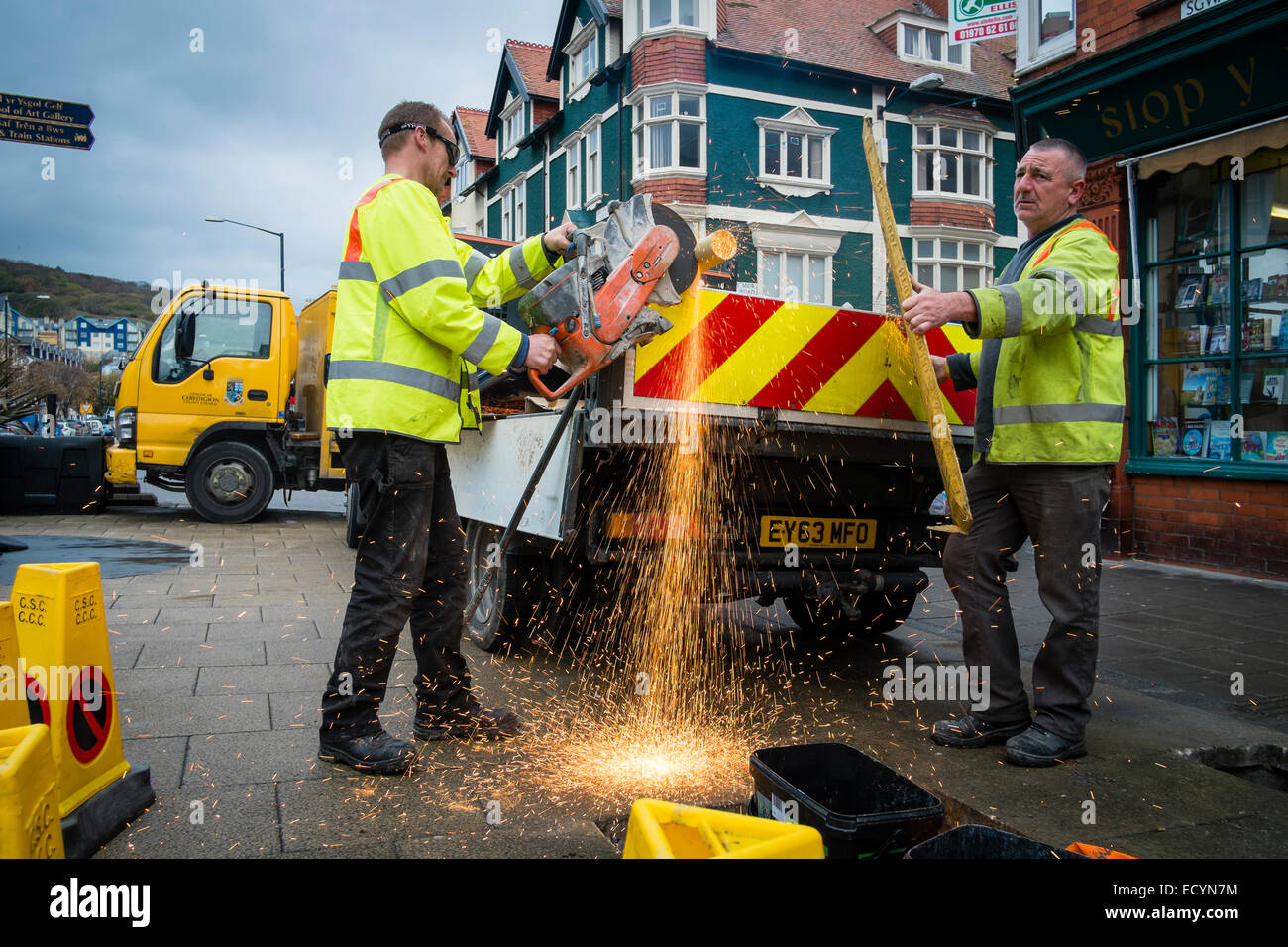 A two-man crew of Ceredigion County Council local authority direct labour workers wearing hi-vis yellow jackets Stock Photo