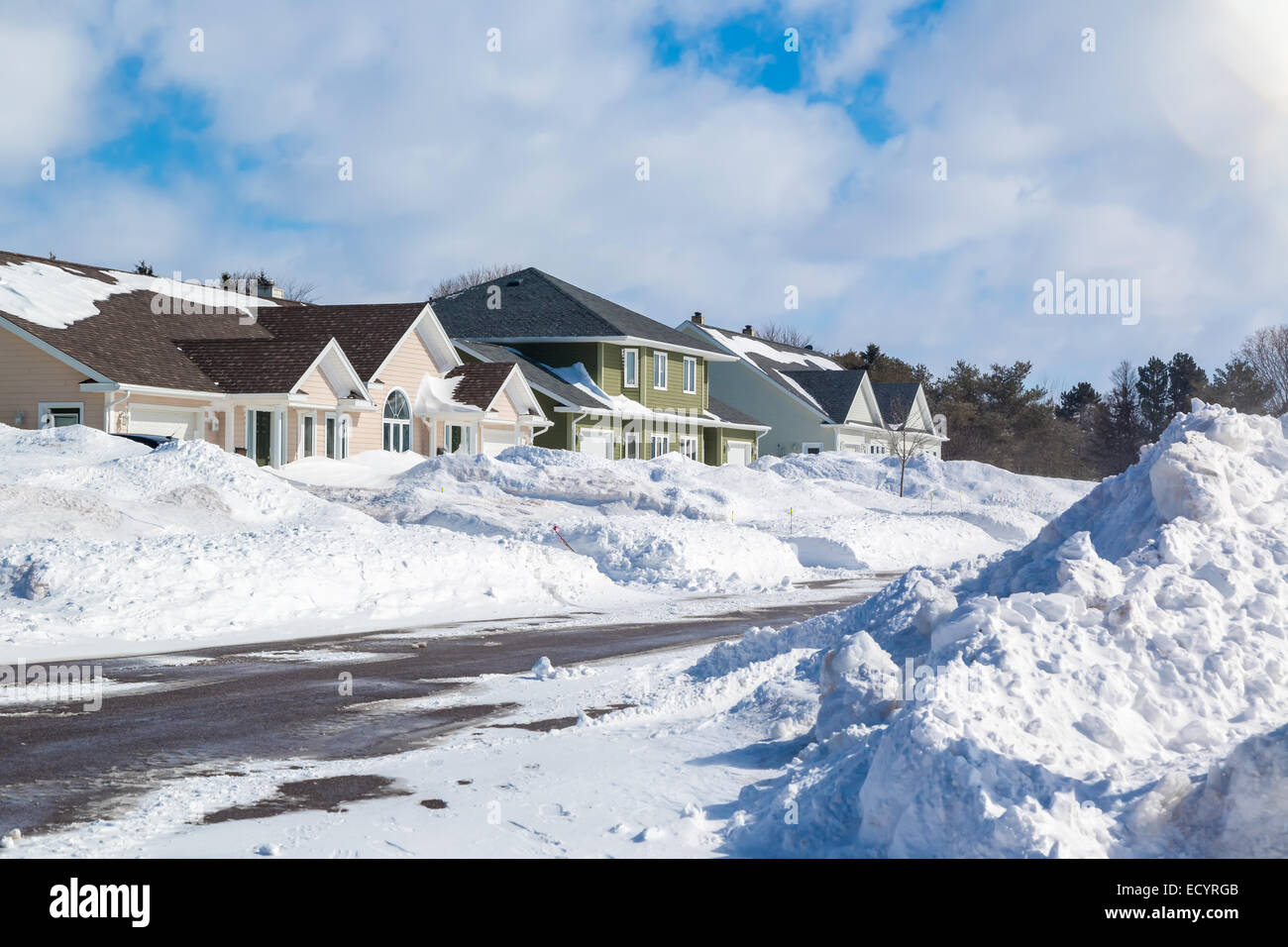 Piles of snow from plowed roads in the suburbs. - Stock Image