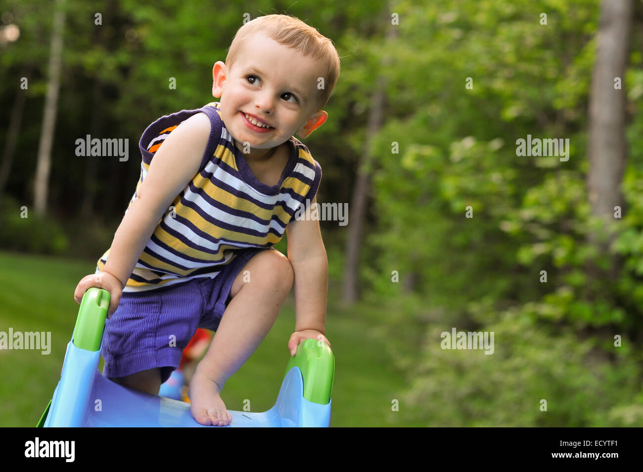 A toddler boy in a striped tank top plays on a plastic slide in summer. - Stock Image
