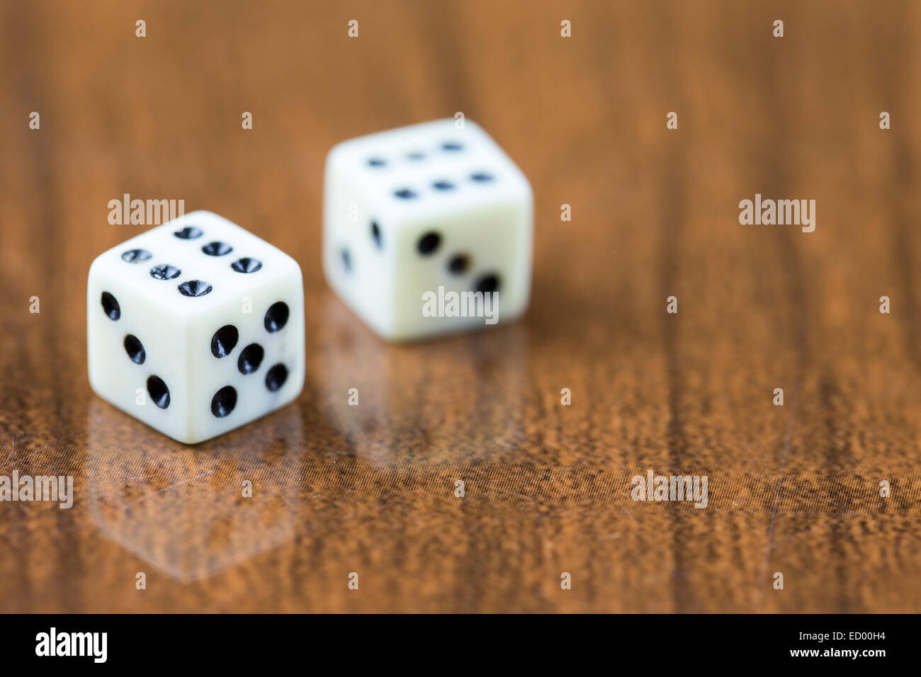 Two dice on a wooden background showing two sixes - Stock Image