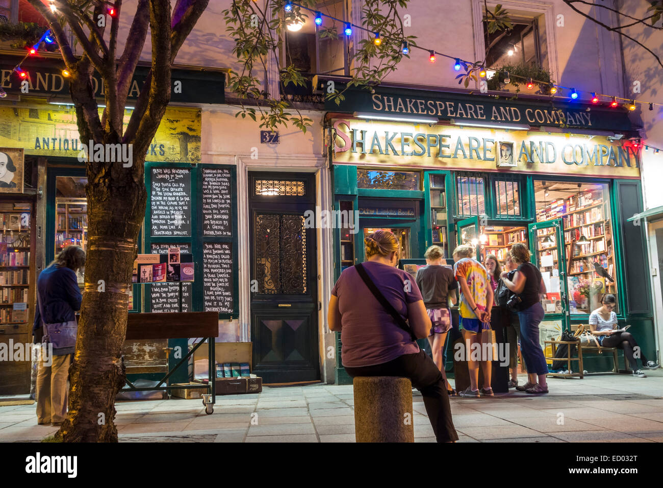 Paris. Young people reading, browsing, shopping at famous Shakespeare and Company Paris Bookshop Book Shop Book - Stock Image