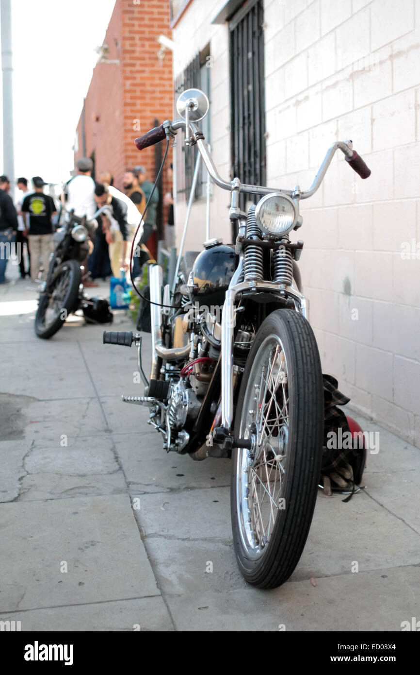 An old motorcycle is parked in front of a party - Stock Image
