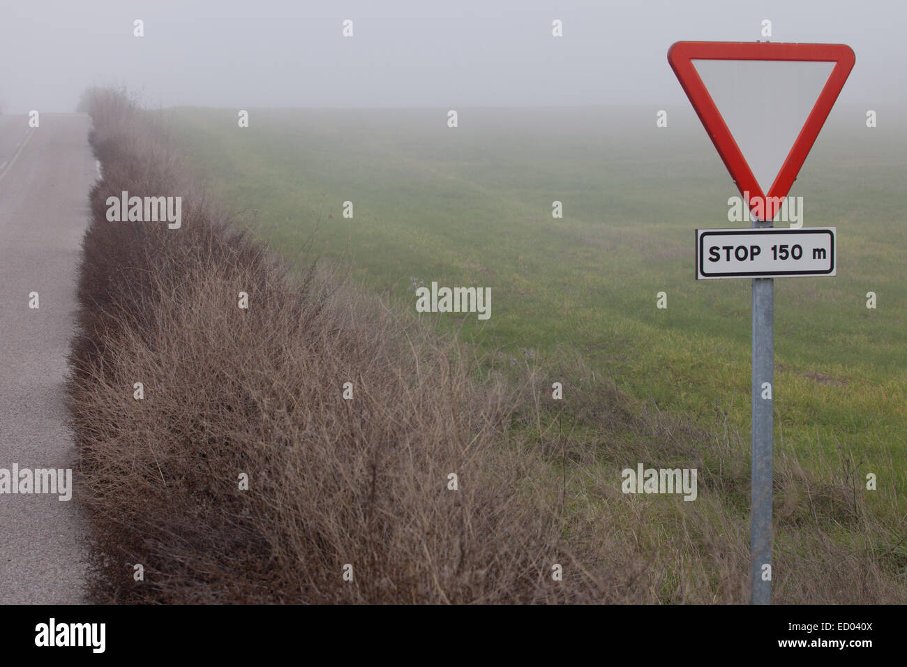 Metal pole with traffic signal yield sign in rural road next to Ahillones, Badajoz, Spain - Stock Image