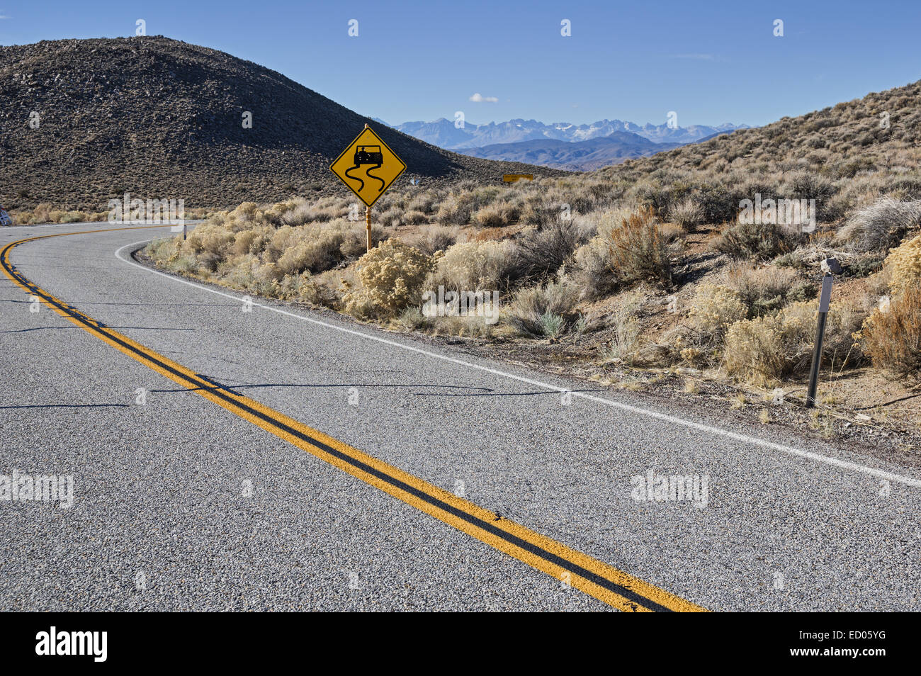 curved road with slippery road sign and distant mountains - Stock Image