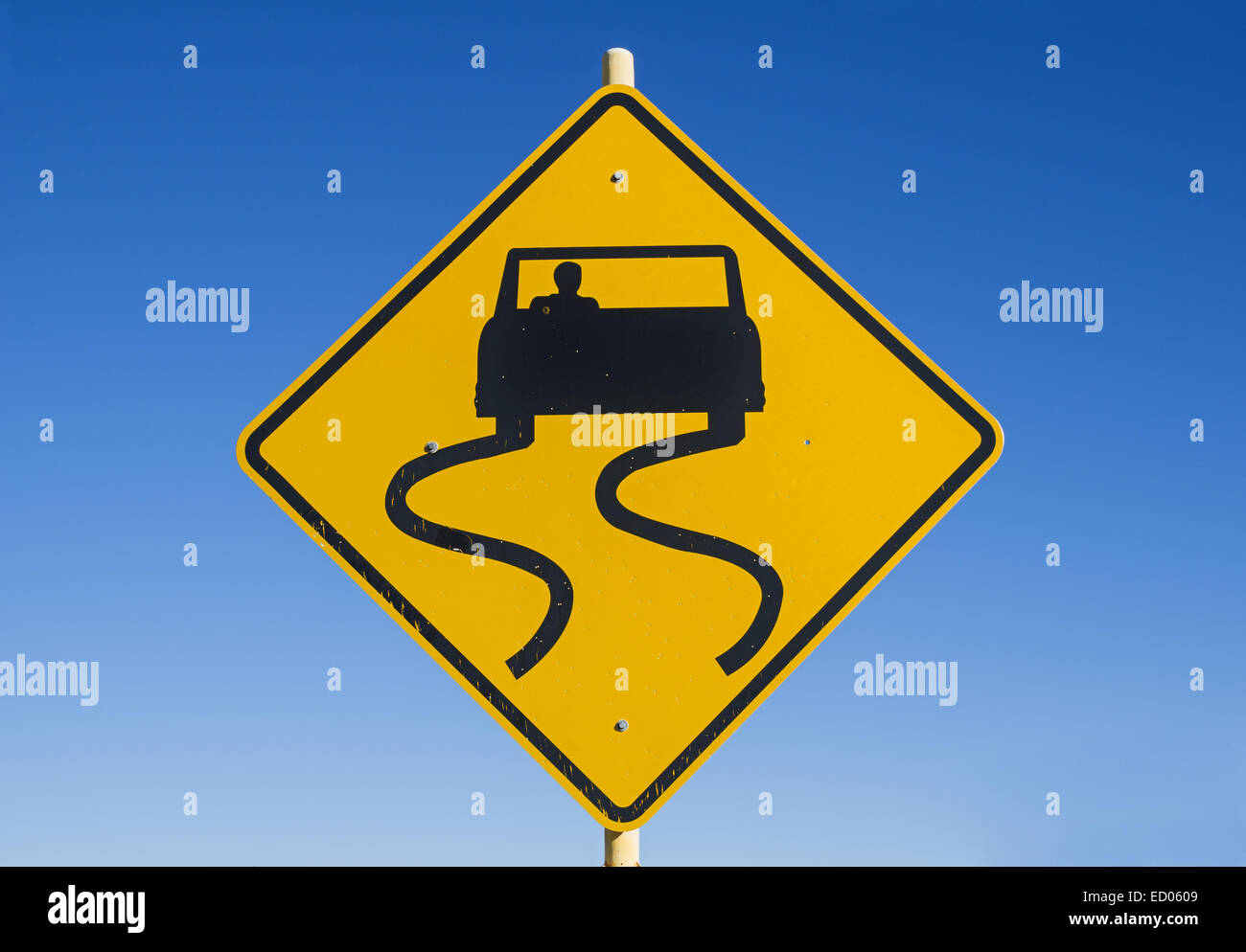 yellow and black caution slippery road sign with car and skid marks with blue sky background - Stock Image