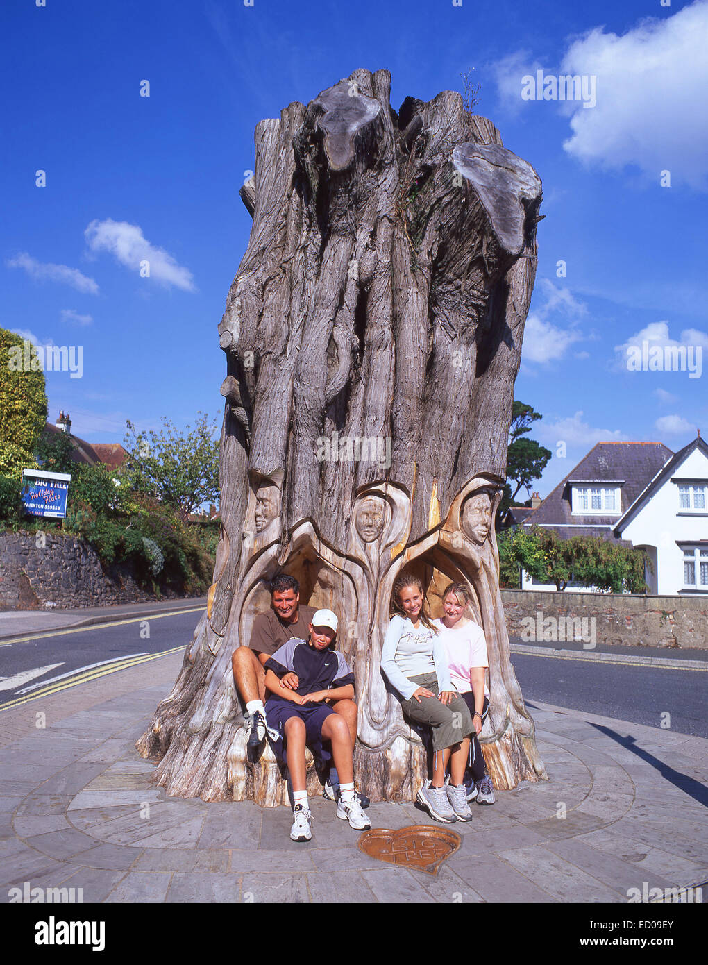 Family sitting in The Big Carved Tree, Paignton, Tor Bay, Devon, England, United Kingdom - Stock Image