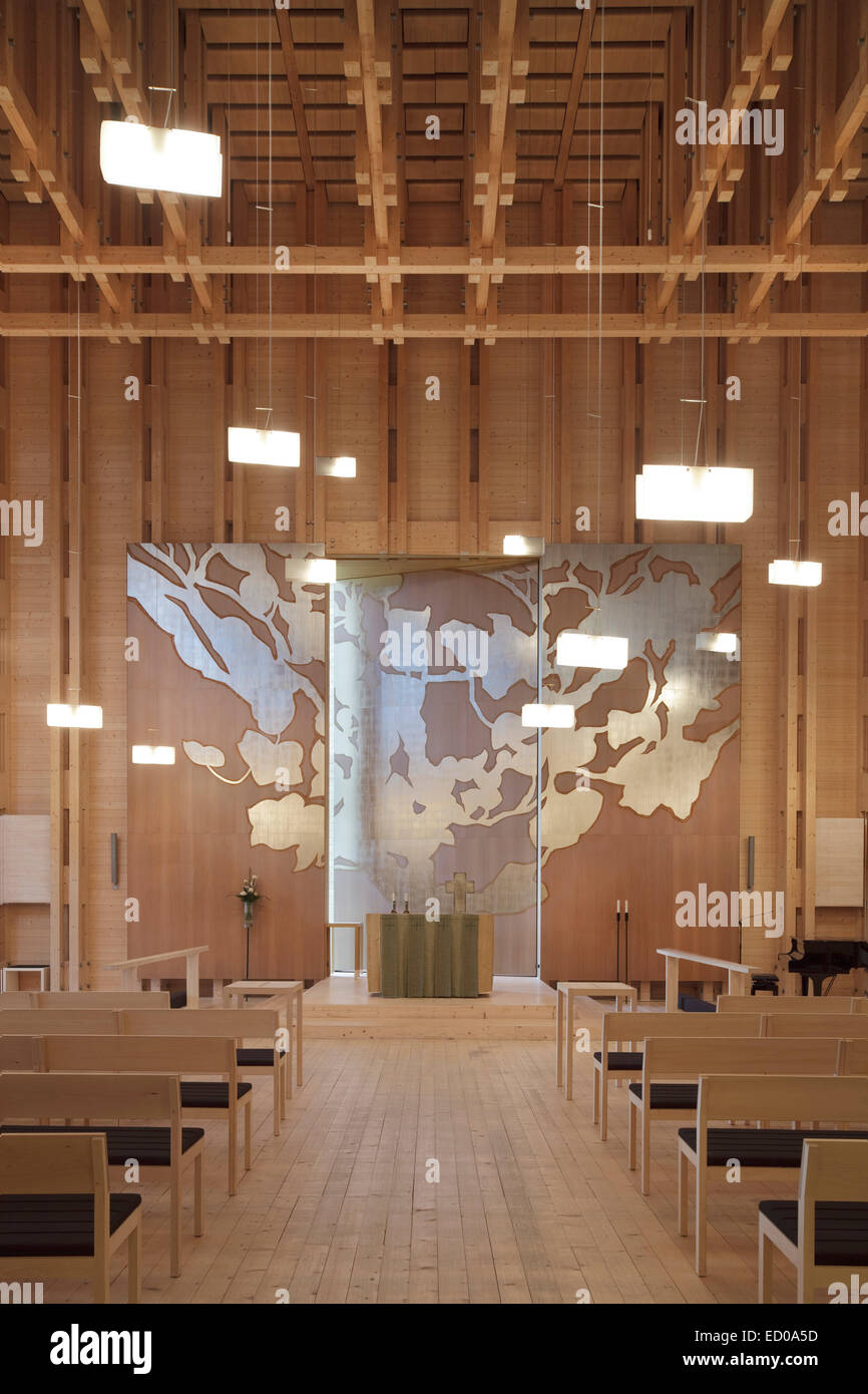 Viikki Church, Helsinki, Finland. Architect: JKMM Architects, 2005. Interior in spruce, with aisle flanked by pews - Stock Image