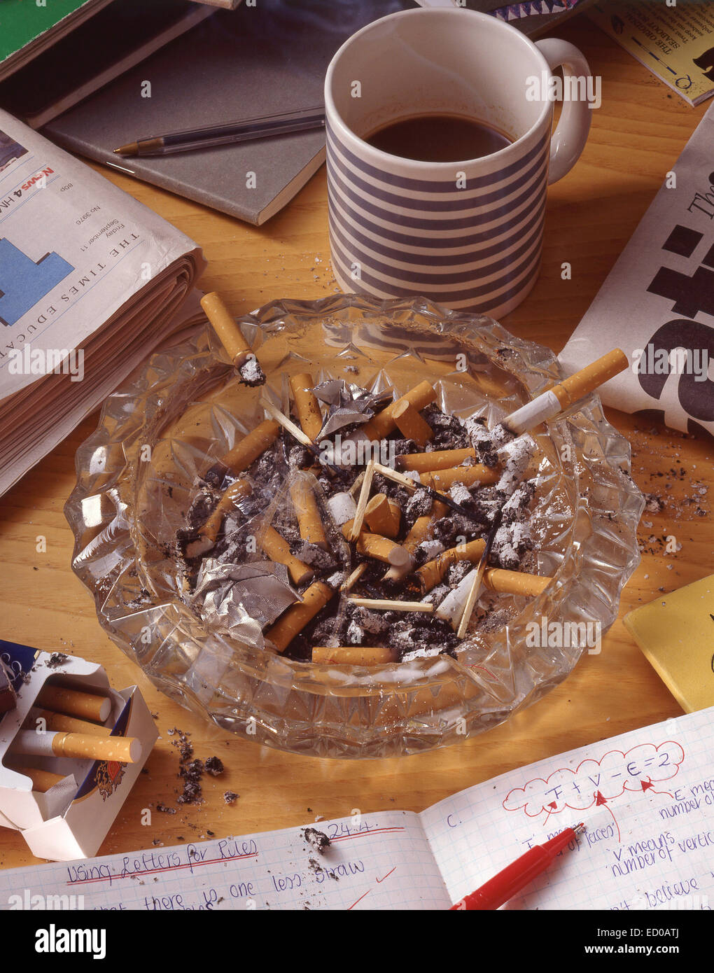 Work desk showing ashtray filled with cigarette butts - Stock Image