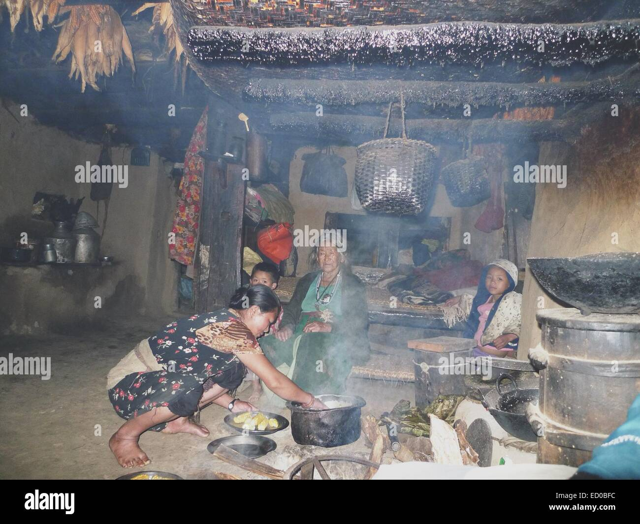 Nepal, Family with children (8-9) cooking corns - Stock Image