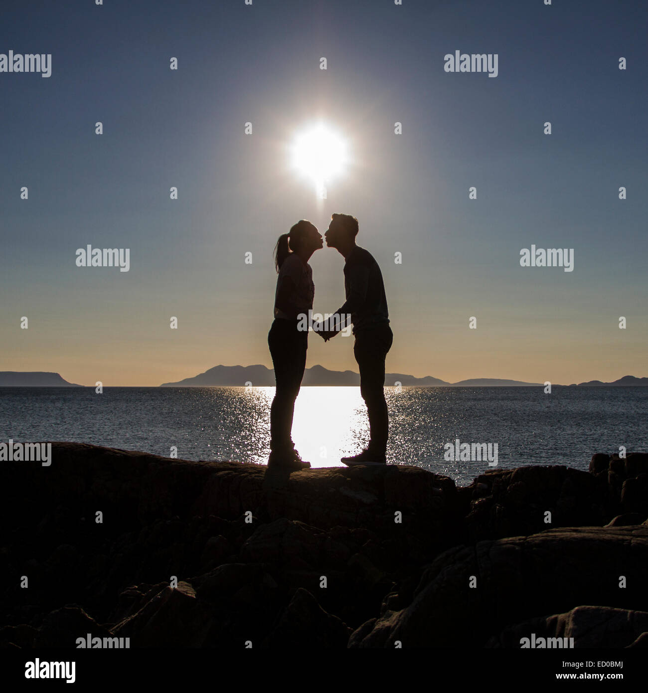 Happy Couple Sitting On Sandy Beach Embracing Kissing: Couple Kissing Silhouette Stock Photos & Couple Kissing
