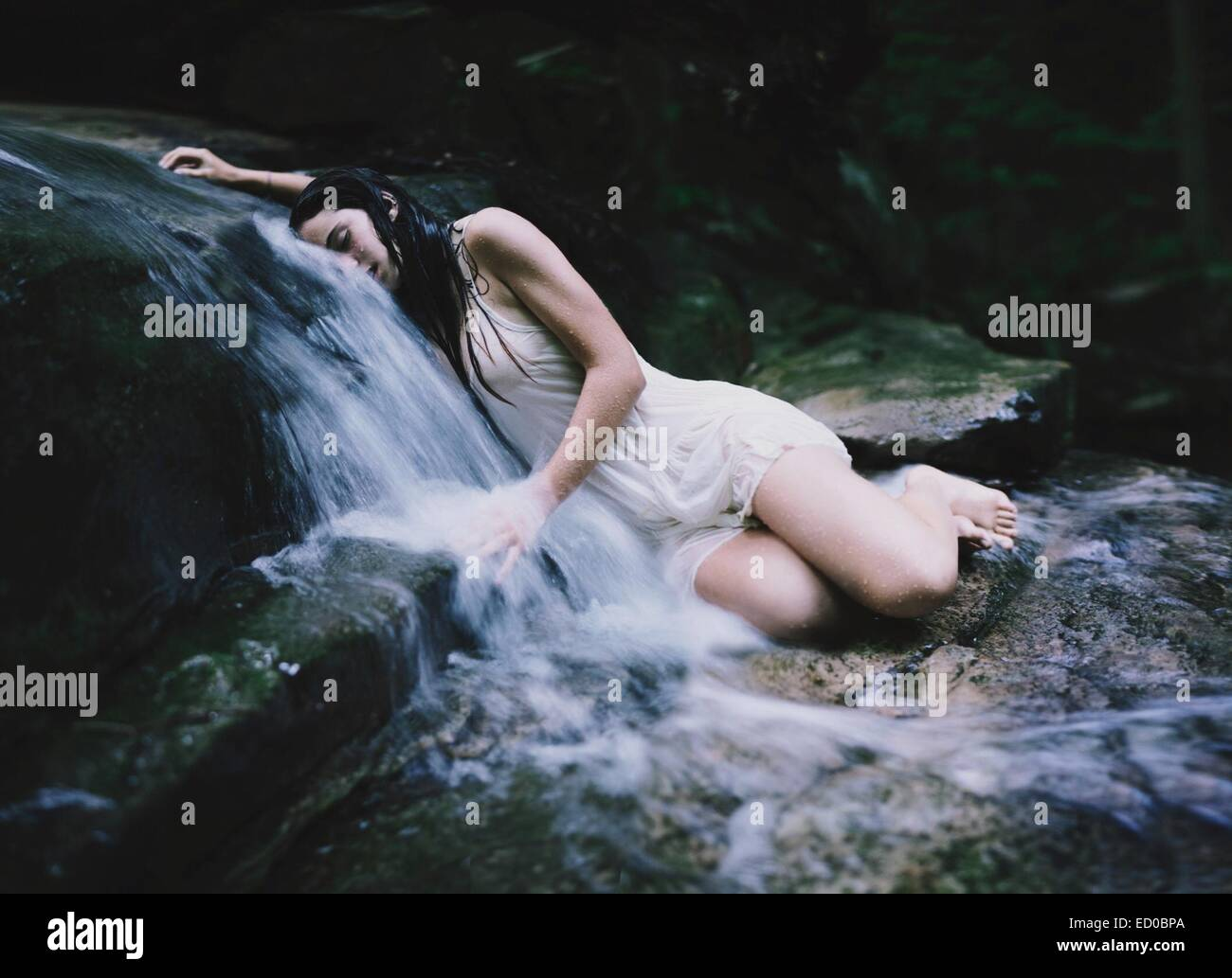 Young woman lying on small waterfall - Stock Image