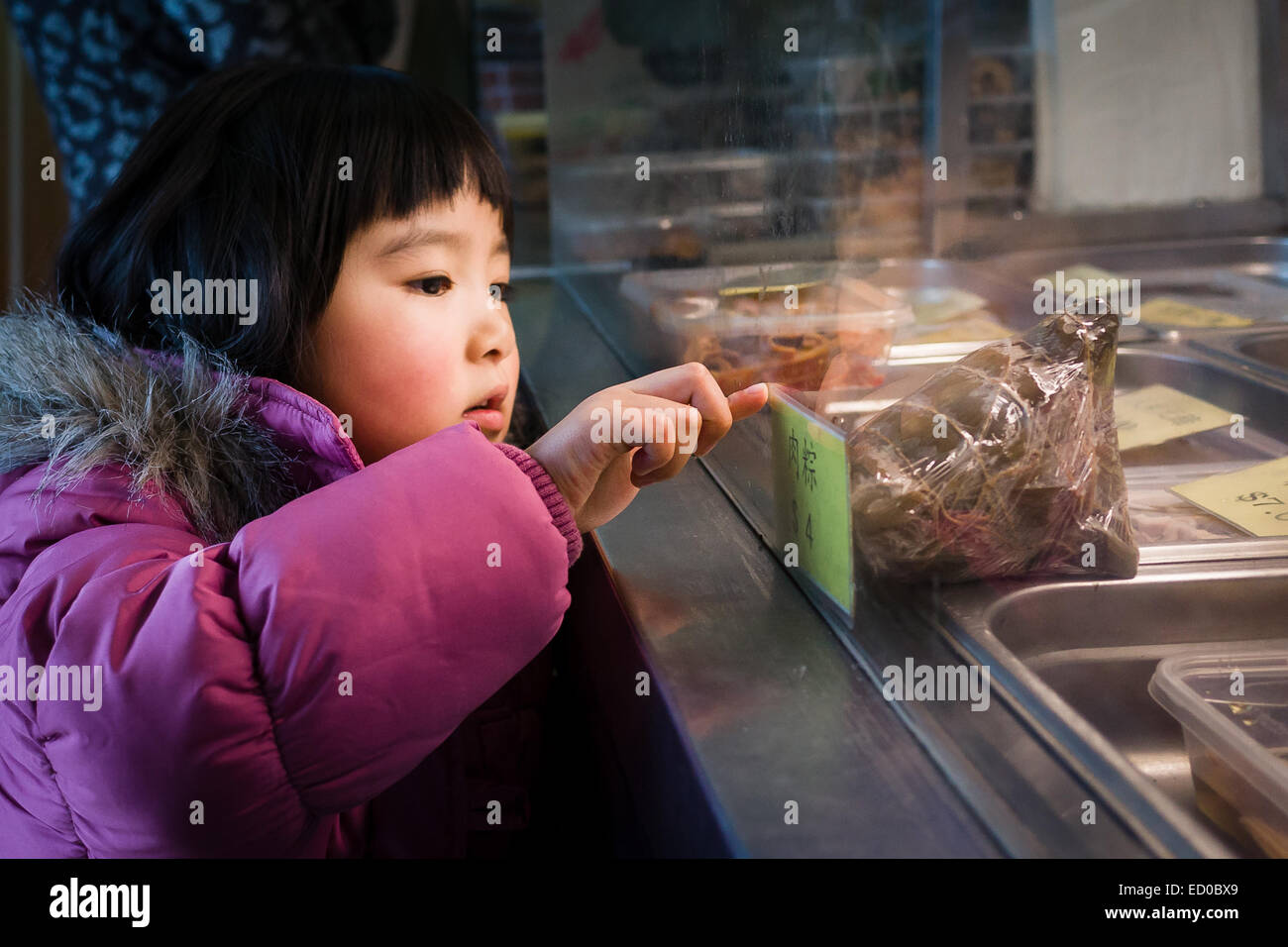 Girl wearing pink jacket looking at display - Stock Image
