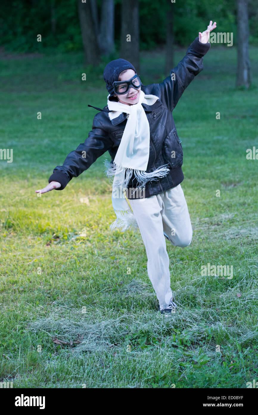 Boy running with arms outstretched pretending to be airplane - Stock Image