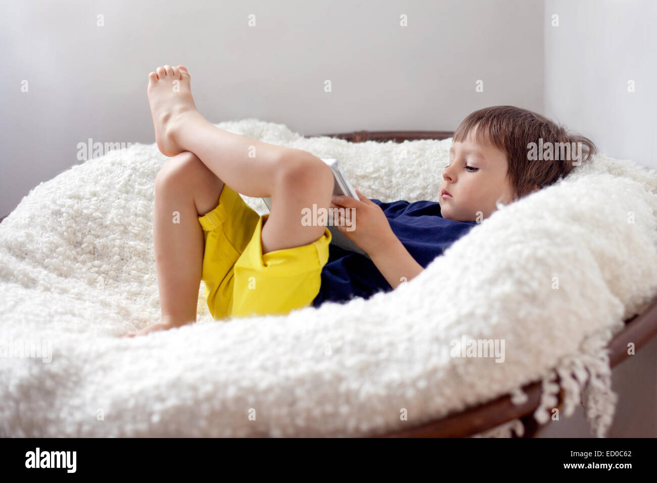 Boy (2-3) lying down in armchair with digital tablet - Stock Image