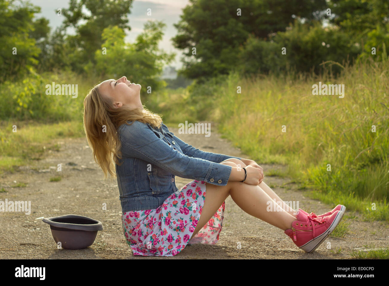 Blonde girl (14-15) sitting on dirt road and laughing - Stock Image