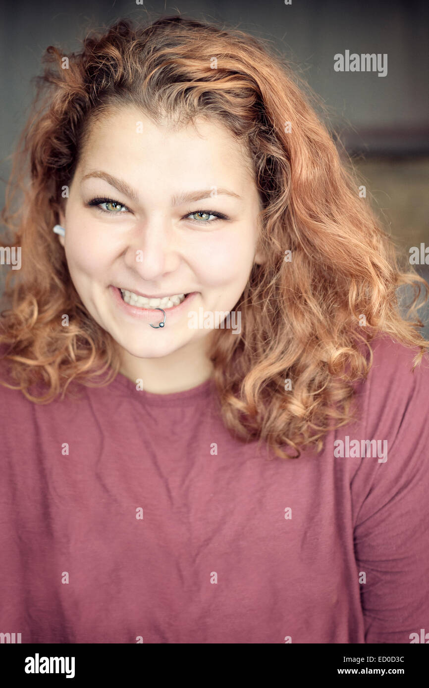 Smiling young woman with lip ring - Stock Image