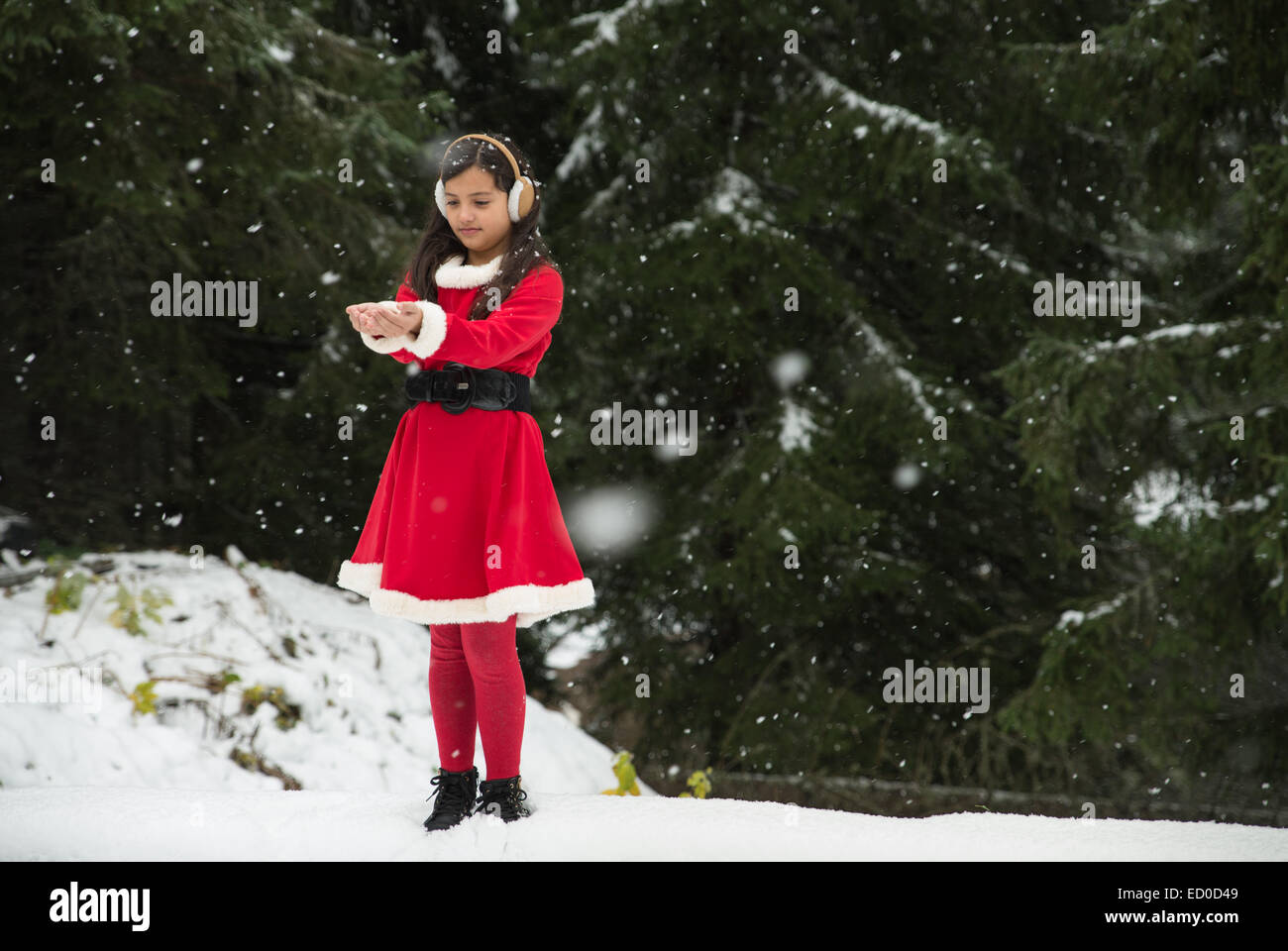 Girl wearing Christmas Santa outfit catching snow - Stock Image