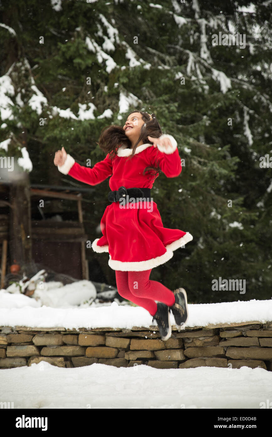 Girl wearing Christmas Santa outfit jumping in the air - Stock Image