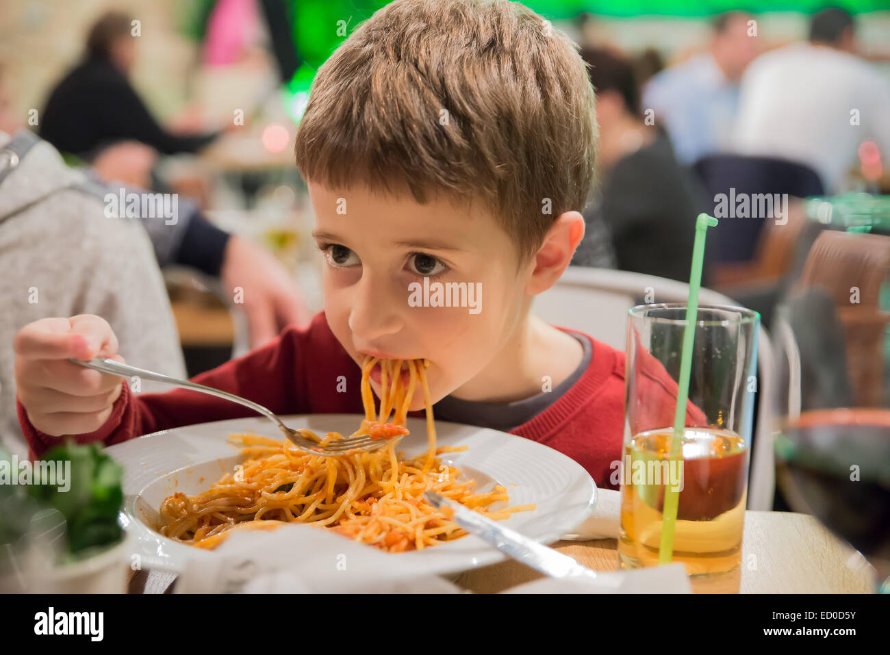 Boy sitting in a restaurant eating spaghetti - Stock Image