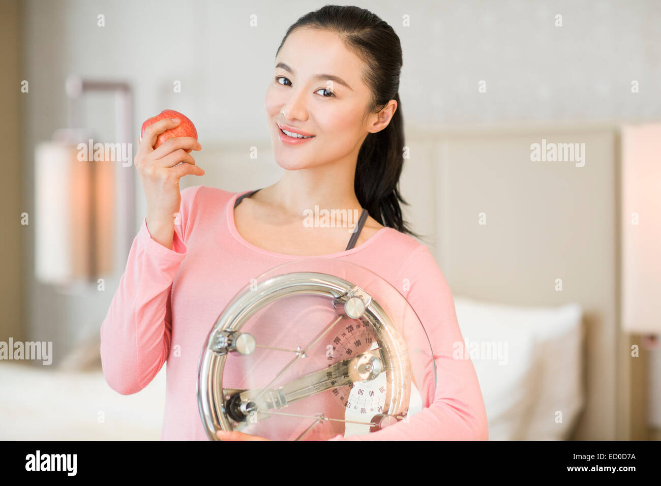 Happy young woman holding weight scale and apple - Stock Image