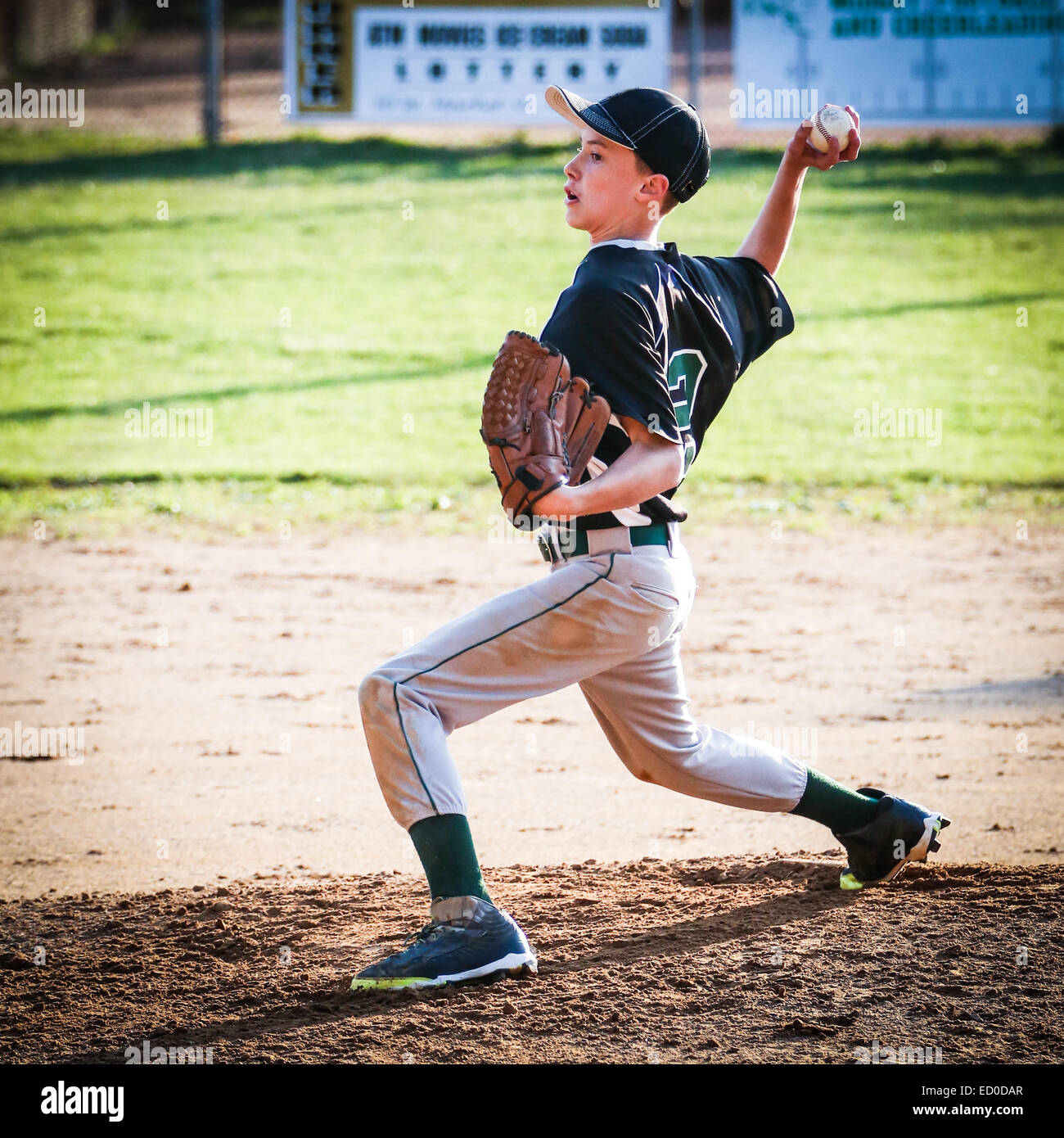 USA, Young boy (10-11) pitching on pitchers mound - Stock Image