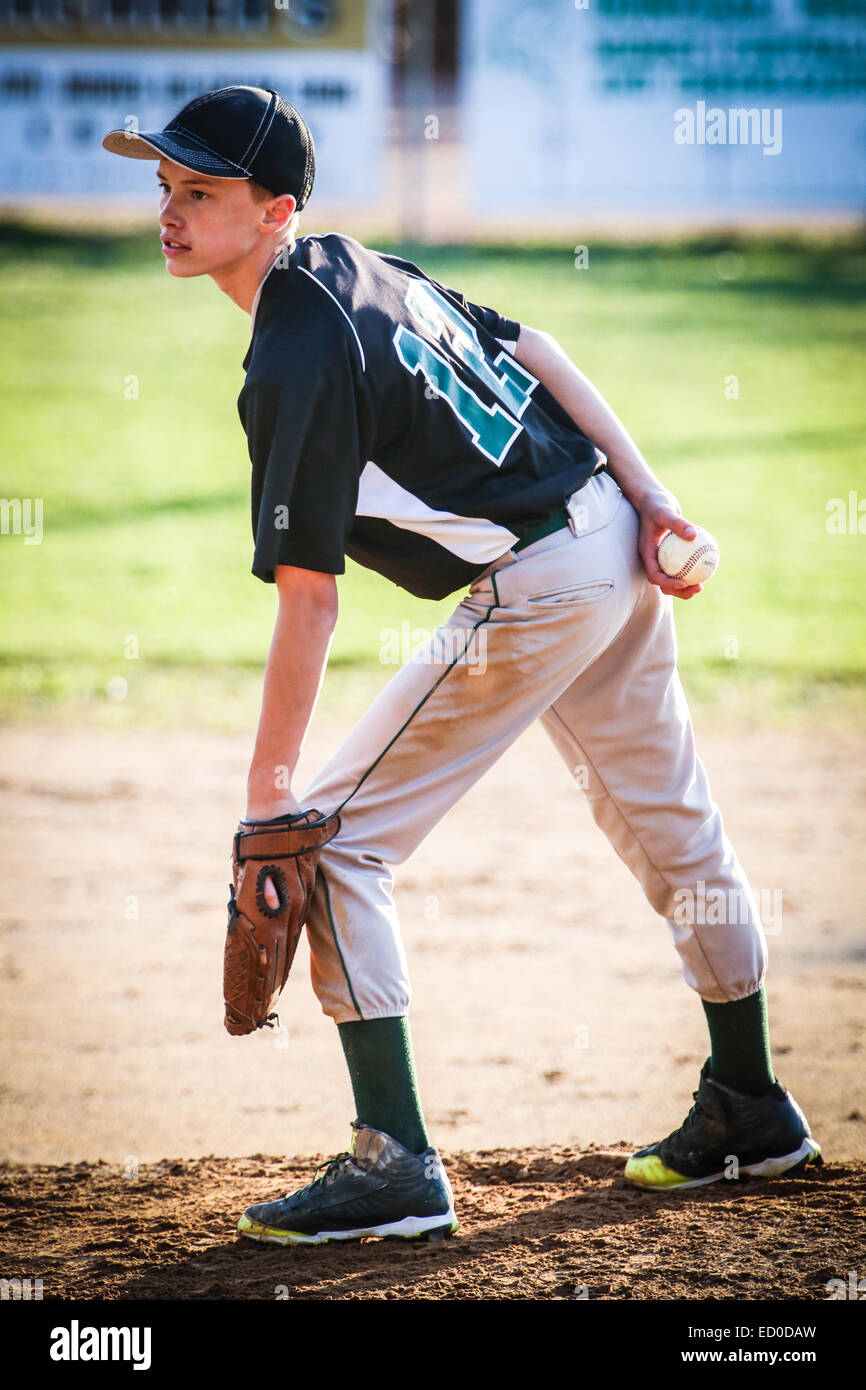 Boy standing on pitchers mound playing baseball - Stock Image
