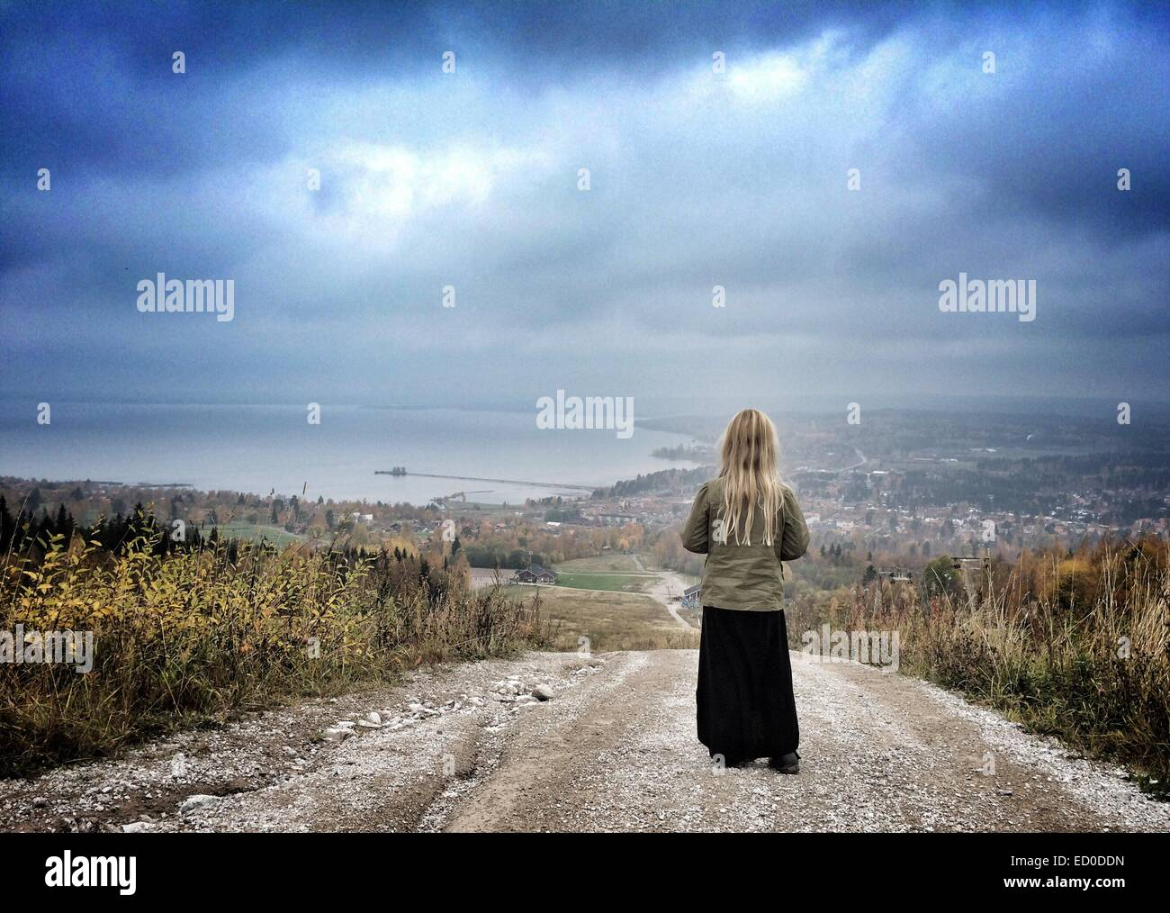 Sweden, Dalarna, Young girl (6-7) standing on top of hill and looking at city and lake below - Stock Image