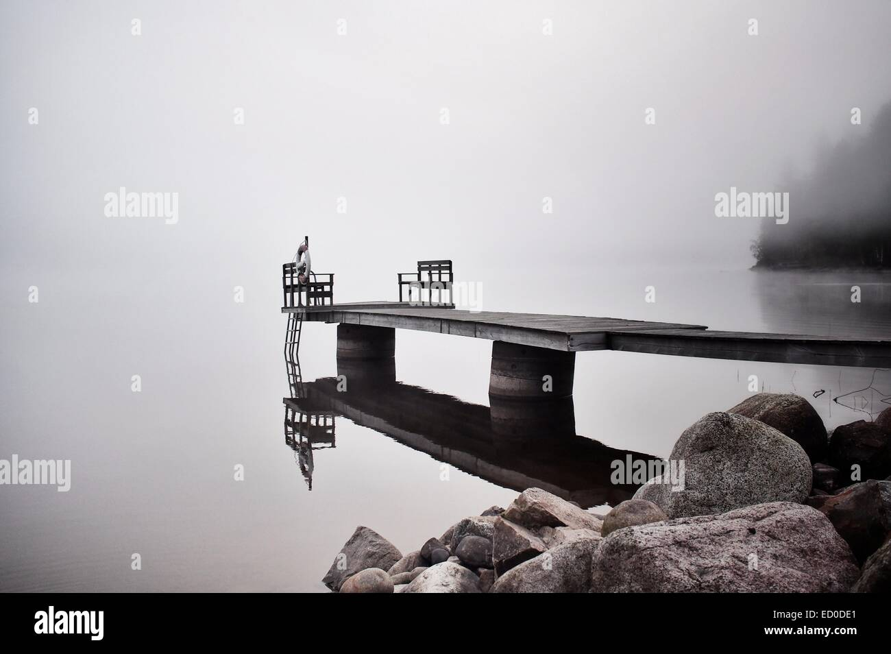 Sweden, Dalarna, Pier reflecting in surface of water in misty, foggy morning - Stock Image