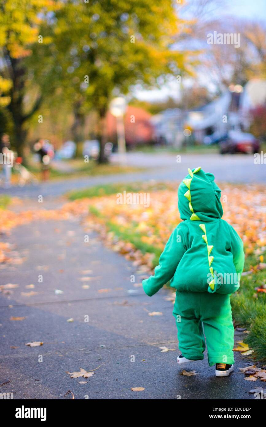 Boy in dinosaur costume walking on sidewalk - Stock Image