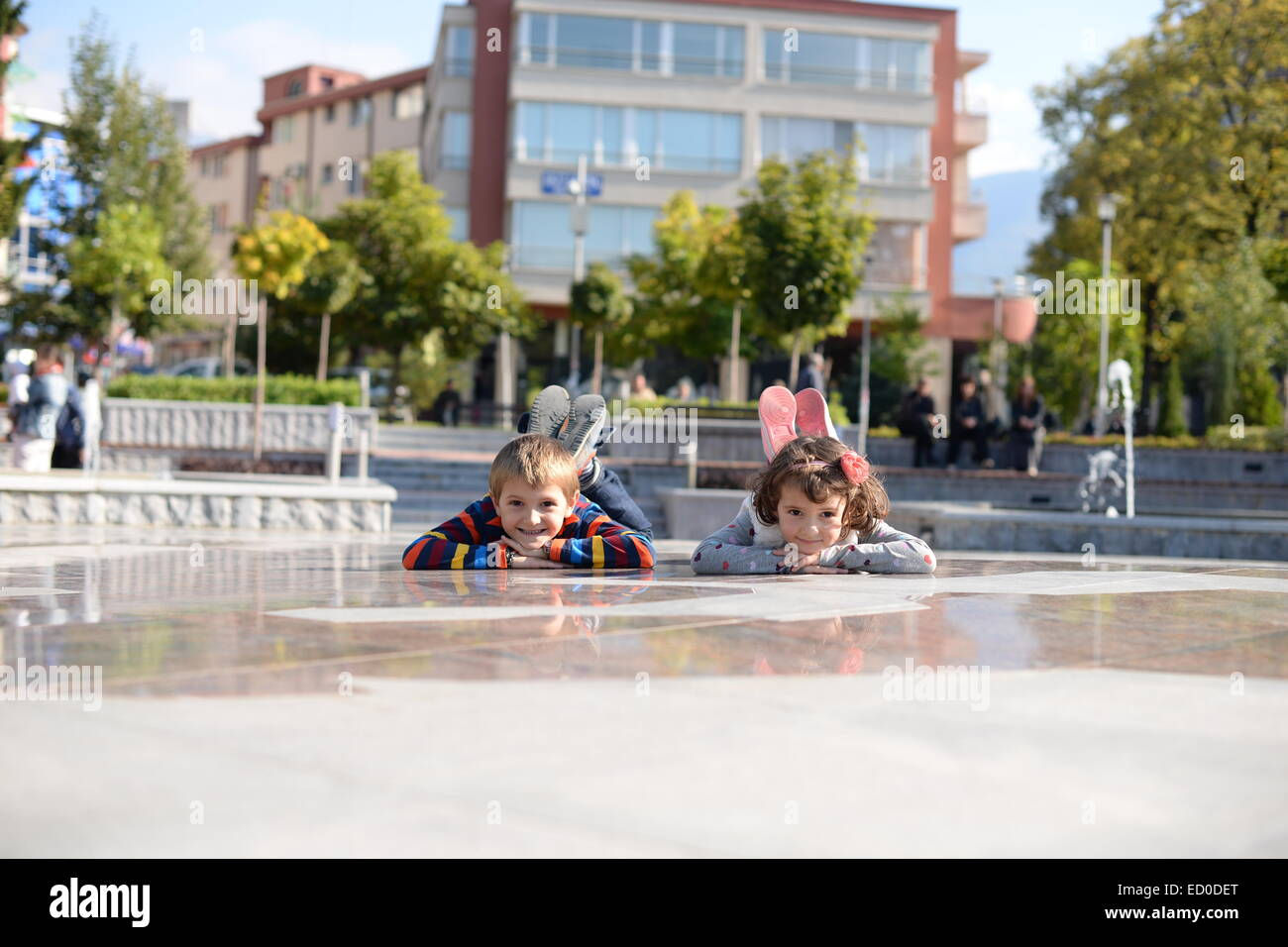 Little boy (6-7) and girl (4-5) playing outside - Stock Image