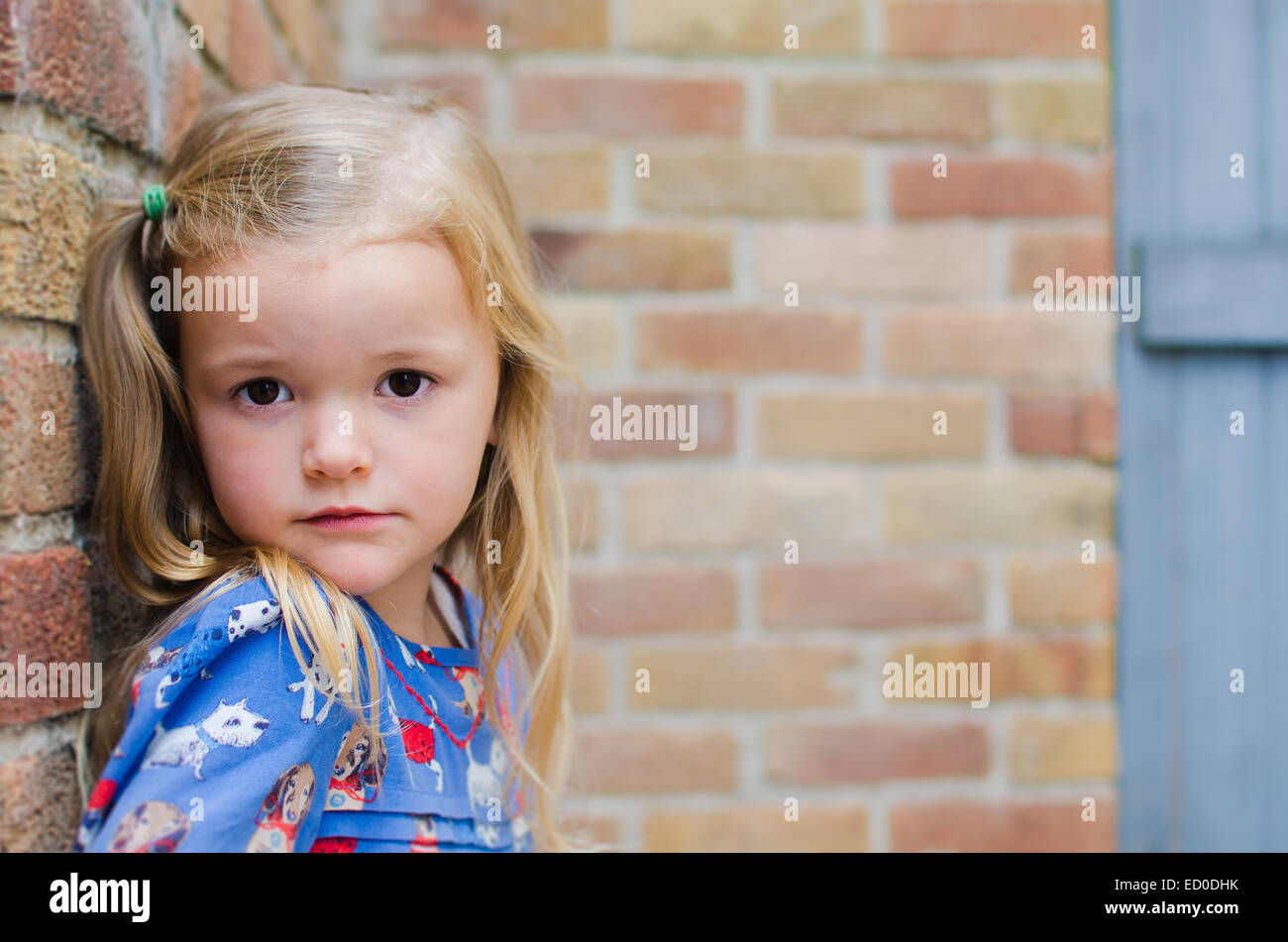 Portrait of girl leaning against brick wall - Stock Image