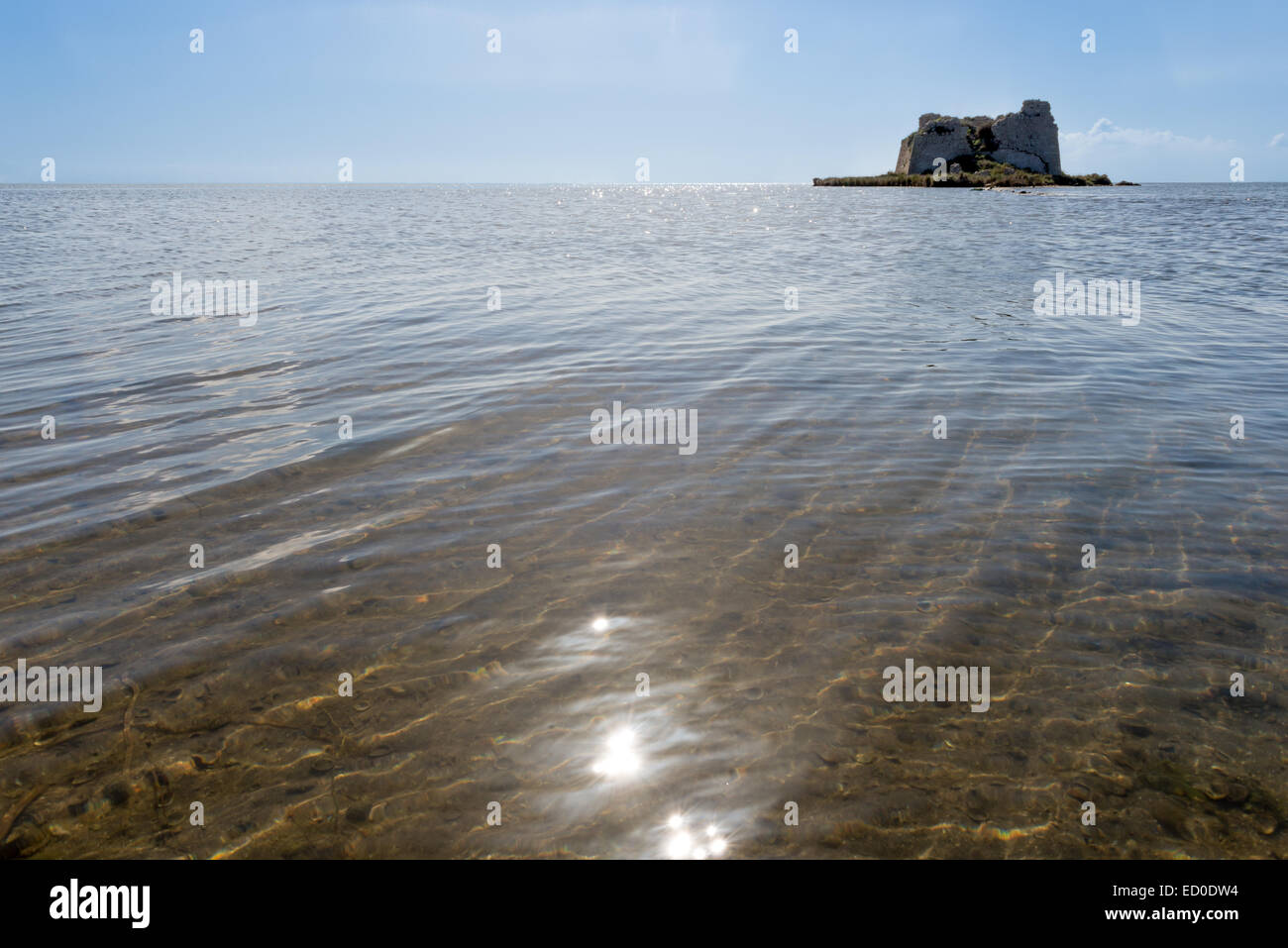 Spain, Catalonia, Tarragona, Alfacs Bay, Close-up view of calm shallow sea with ruins of Sant Joan Tower in distance - Stock Image