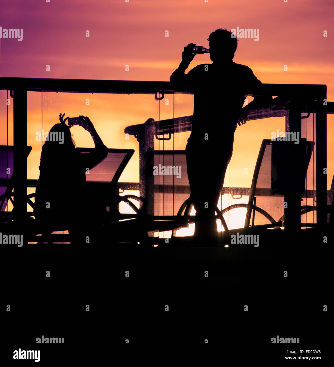 England, Southampton, Silhouettes of couple relaxing on balcony at sunset Stock Photo