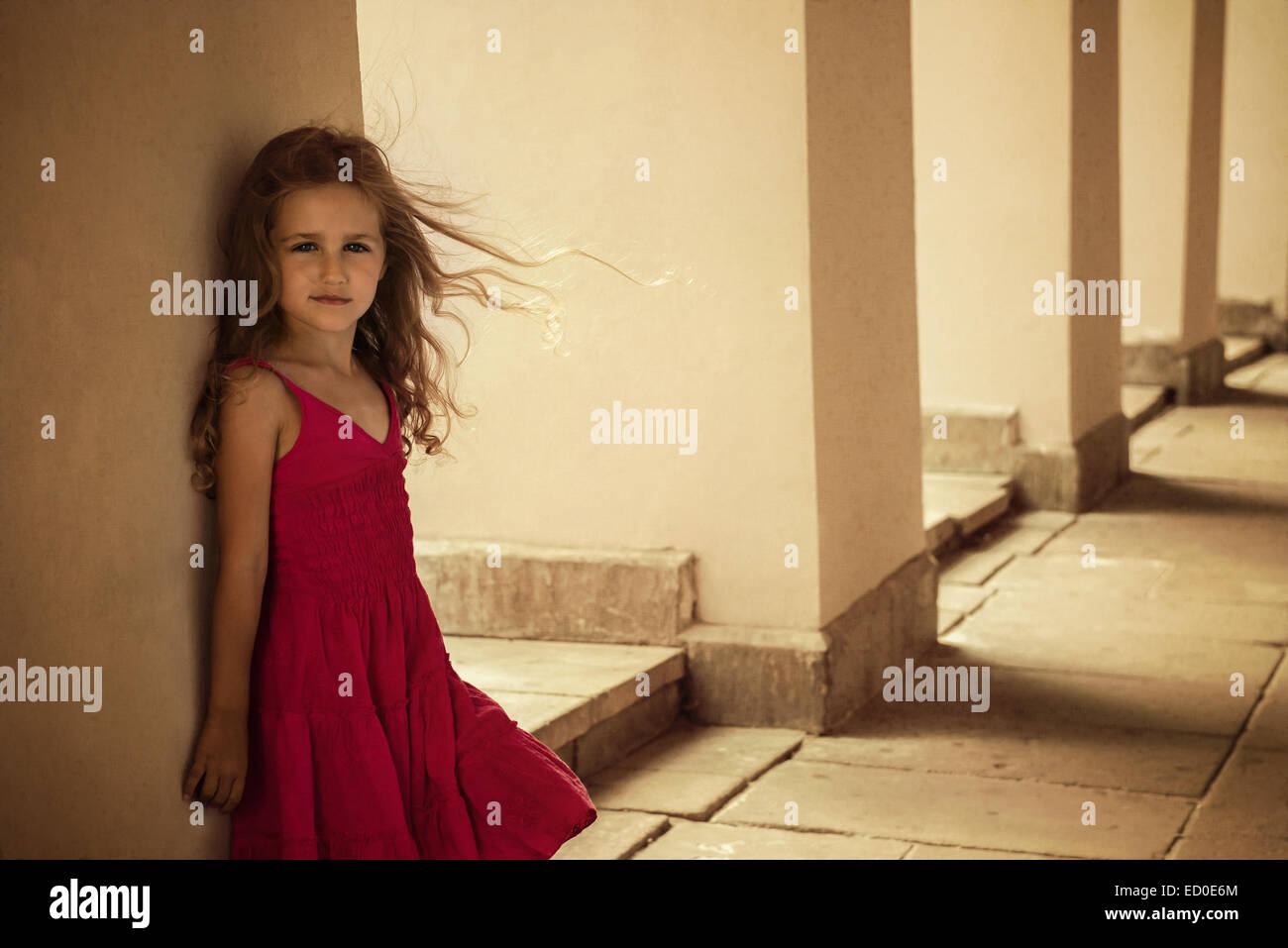 Girl (4-5) posing in red dress - Stock Image
