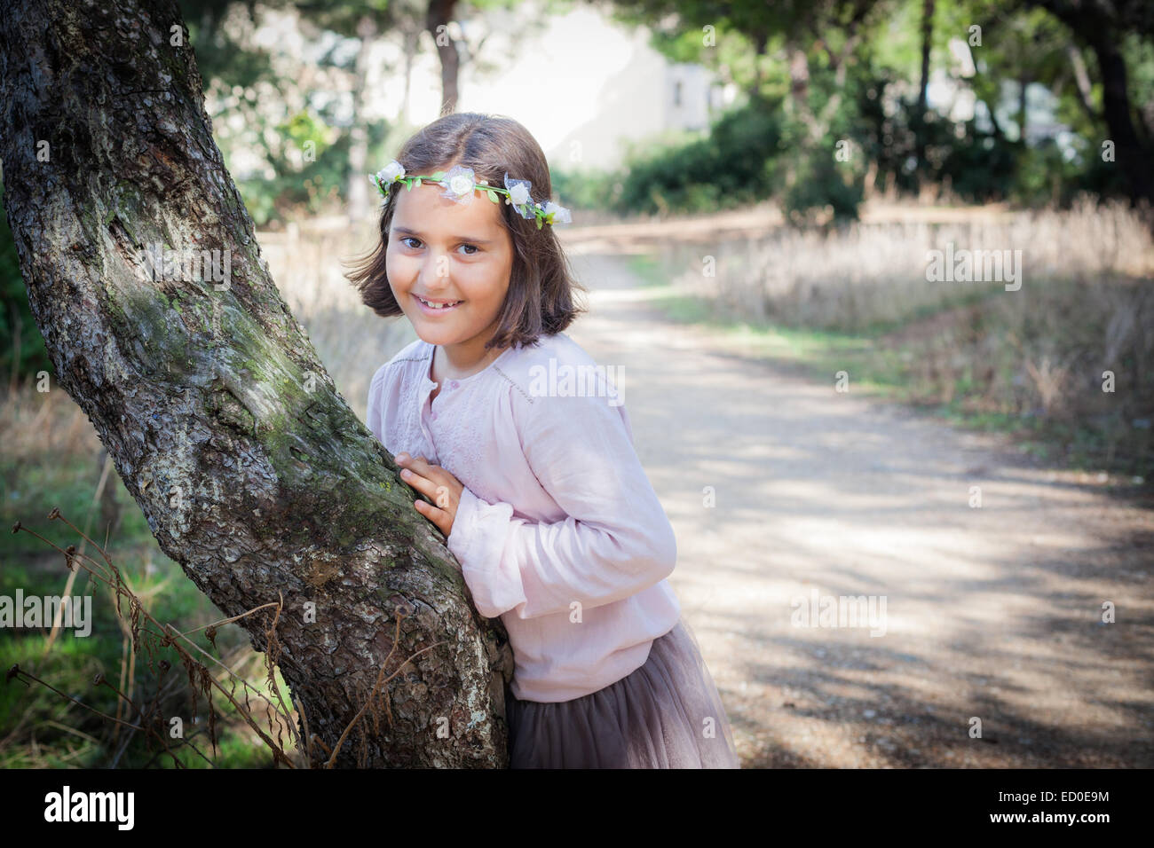 Portrait of girl (6-7) in garland leaning against tree trunk - Stock Image