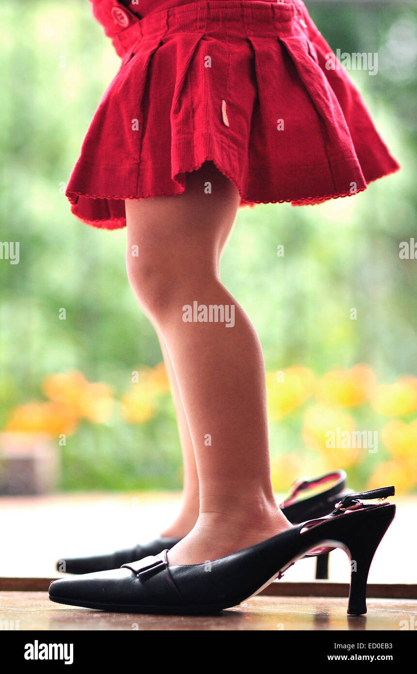 Girl wearing her mother's high heel shoes Stock Photo